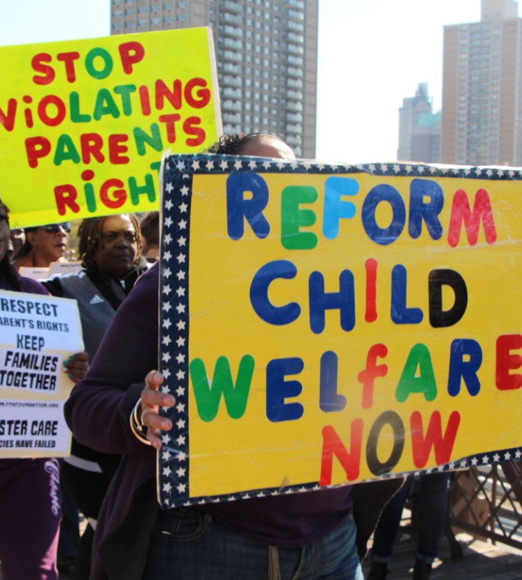 Activists hold protest signs reading 'Reform Child Welfare Now', 'Stop Violating Parents Rights', 'Keep Familes Together'.