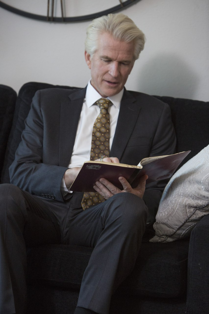 Michael Trainer (Matthew Modine), a high-powered corporate lawyer, sits on a couch and reads from a notebook in 'Foster Boy'.